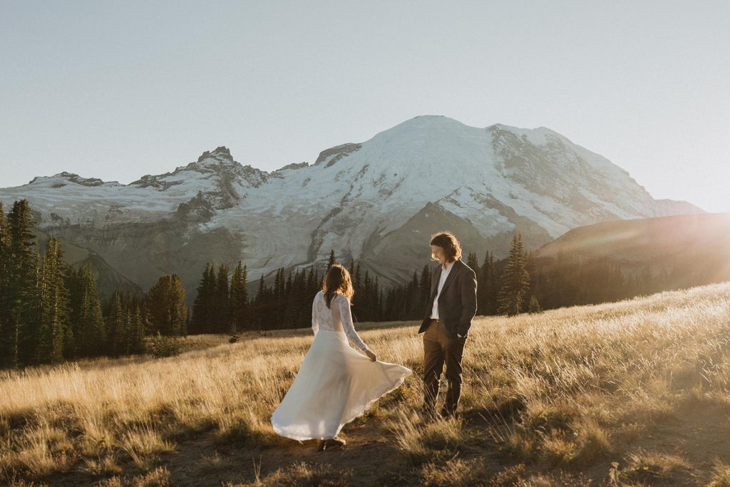 A newlywed couple stand in the mountain fields during their Mount Rainier Cabin Elopement photographed by Alexa Ann Photography, a Seattle Elopement Photographer.