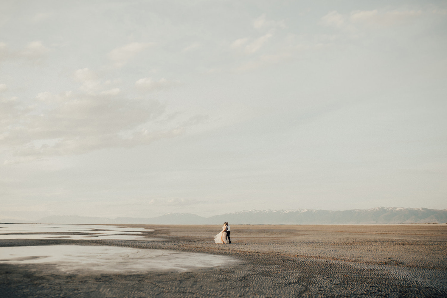 A bride and groom embrace on the horizon of the Bonneville Salt Flats in Utah. Photograph by Alexa Ann Photography, a Seattle elopement photographer.
