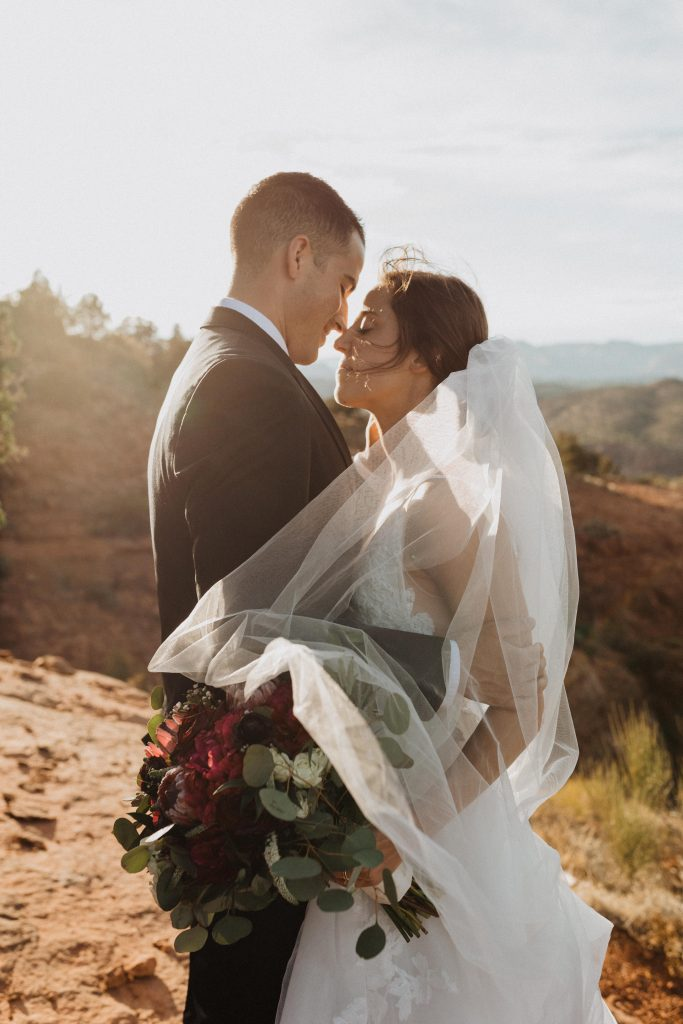 Bride and groom embrace in the desert during their adventurous Tlaquepaque wedding in Sedona, Arizona photographed by Alexa Ann Photography.