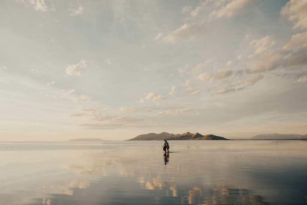 Image of a couple holding hands while walking across the Bonneville Salt Flats, photographed by Alexa Ann Photography.