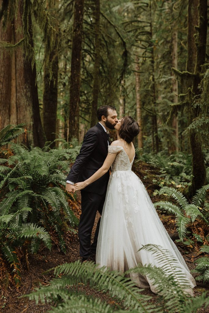 A newlywed couple kiss while standing in the woods of Olympic National Park during their elopement photographed by Alexa Ann Photography