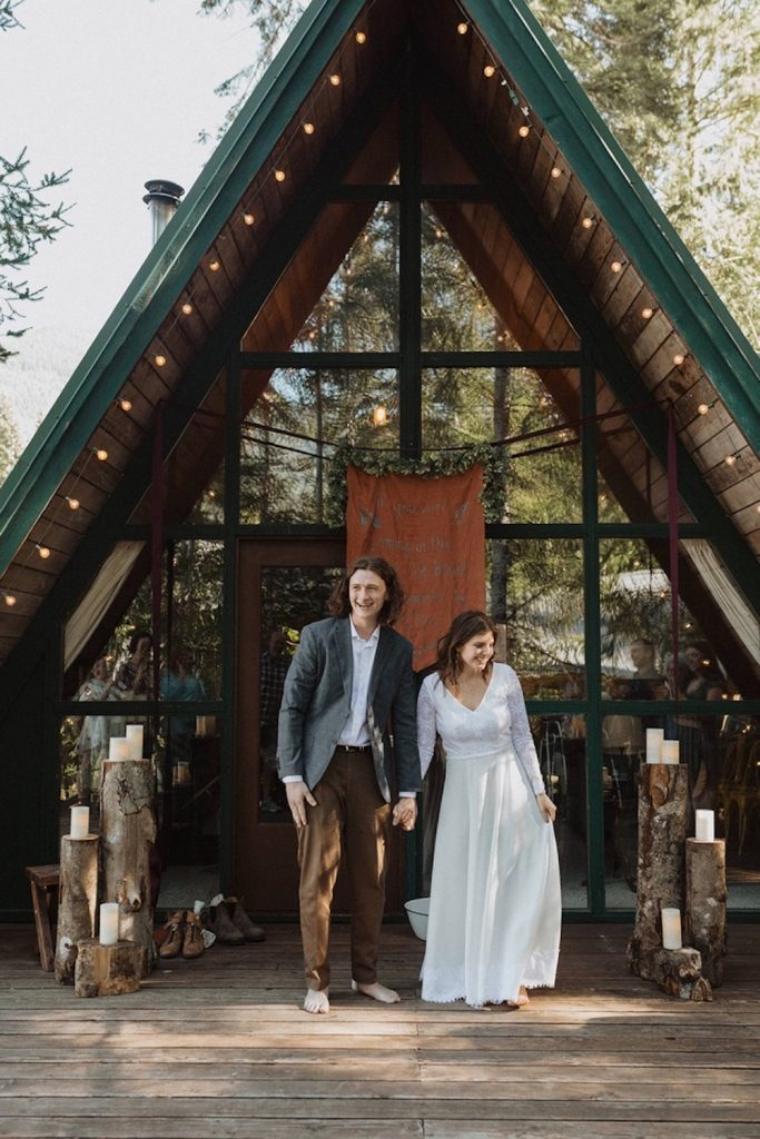 Couple smile as they pose in front of the Spacious, Bright Cabin near Mt Rainier