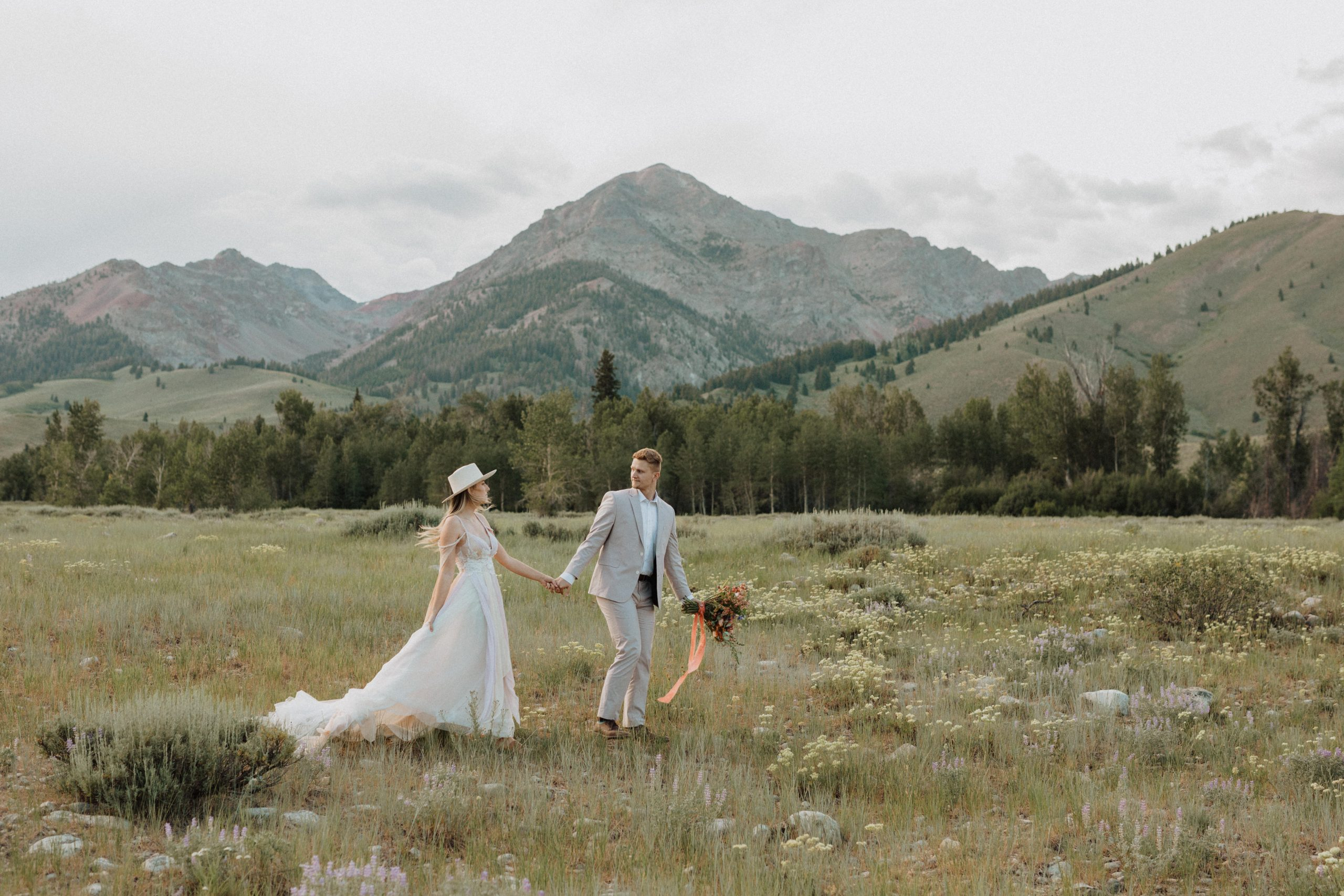 Bride and groom strolling through the grassland hand-in-hand at Sawtooth Wilderness, taken by Alexa Ann Photography