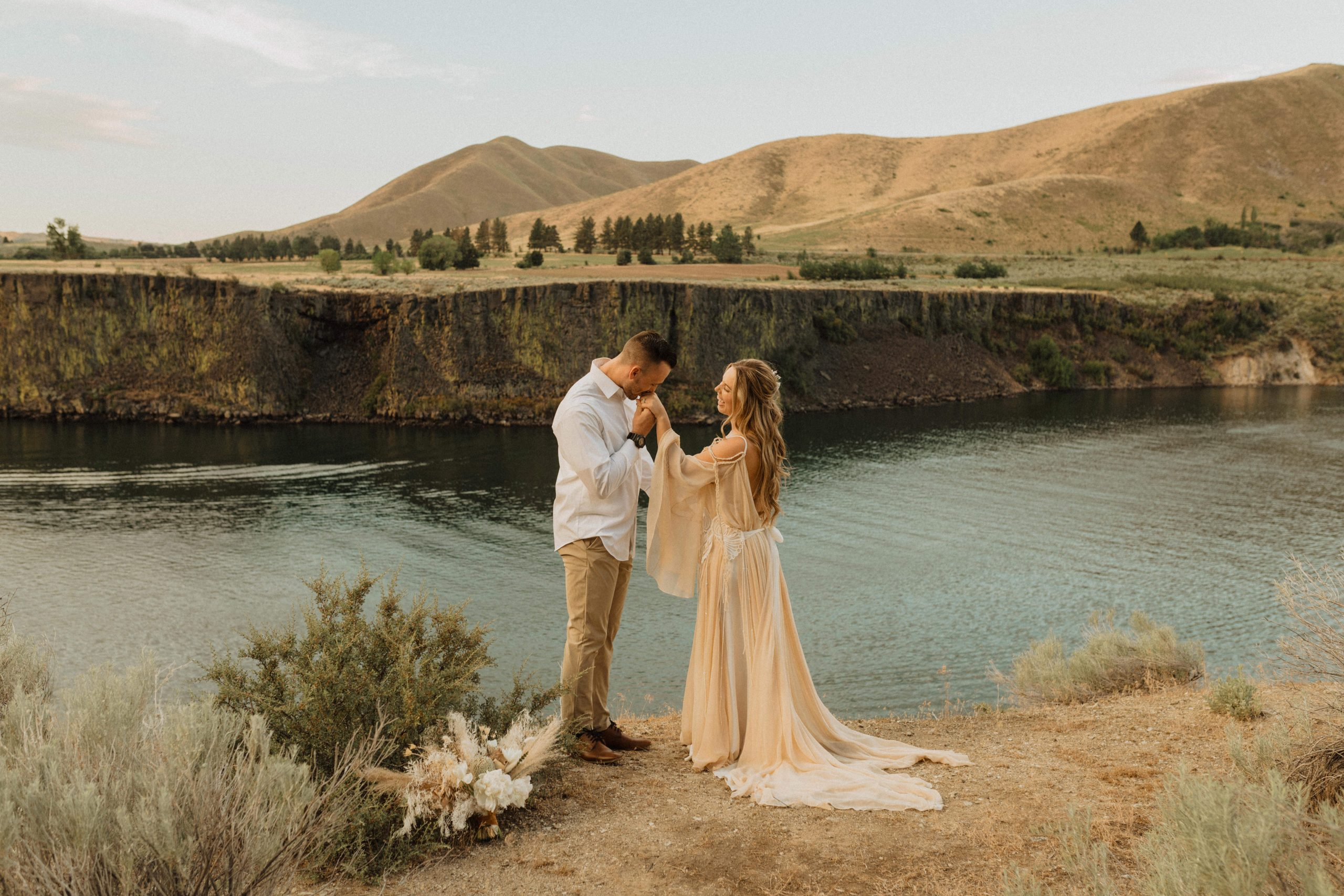 Groom takes bride's hand in his and gives it a light kiss during their elopement at Boise National Forest, captured by Alexa Ann