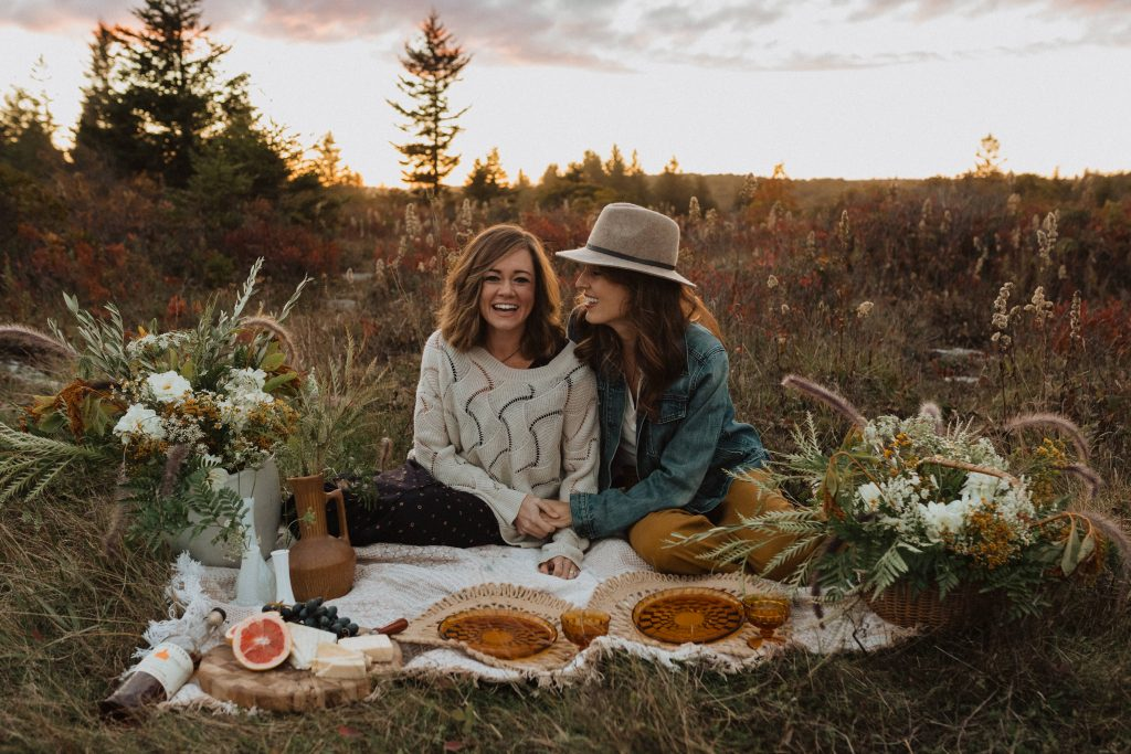 Couple smile as they hold hands on the picnic mat set on the grass at Dolly Sods Wilderness